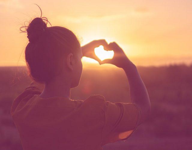 Dame macht mit den Fingern ein Herz gegen das Sonnenlicht
